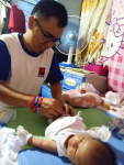 A father changing his baby's diaper.
